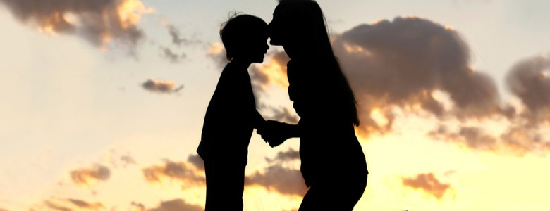 Silhouette of mother kissing her son on the head