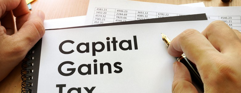 """Hands holding a document that says """"Capital Gains Tax"""""""